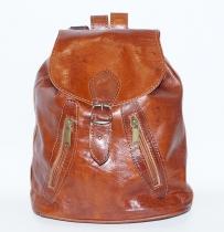 Sac à dos en cuir, rabat avec une fermeture cartable cachée par une boucle ceinture, 2 petites poches zippées en biais devant, 1